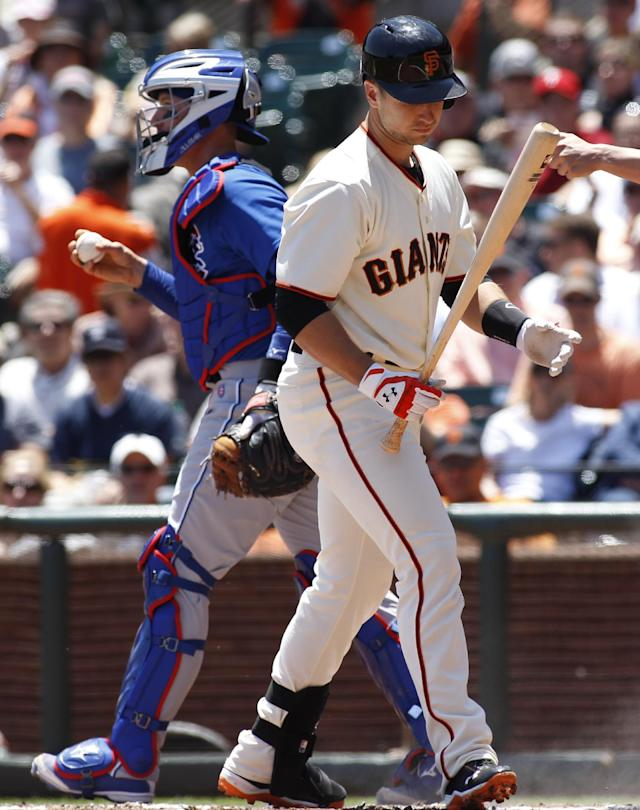 San Francisco Giants' Buster Posey looks at his bat after striking out, next to Chicago Cubs catcher John Baker during the first inning of a baseball game, Wednesday, May 28, 2014, in San Francisco. (AP Photo/George Nikitin)