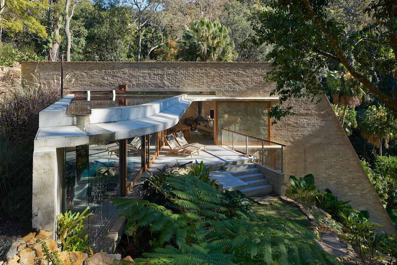 """Cabbage Tree House is set on a steep site in Bayview, a suburb of Sydney. """"It's almost like you're living in a cave that building, but it has great formality to it too,"""" he says. Stutchbury and project architect Emma Trask used the stream below to cool the house and recycled brick to complement the hillside. The vertical building is broken up by a wing with a bedroom, which is topped with a pond. """"The light comes off that pond, which I call a water garden,"""" he continues. """"If you're looking down at the building, I didn't want to look at a roof. I wanted to look at a water garden."""""""