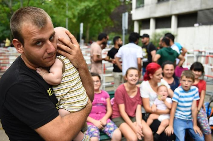 A man holds his baby outside the State Office of Health and Social Affairs Berlin (LAGeSo) where hundreds of refugees are waiting to receive help on August 7, 2015 (AFP Photo/Tobias Schwarz)