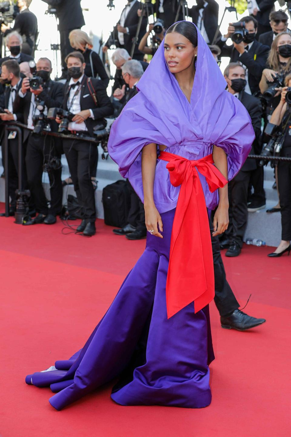 <p>Wearing a purple Valentino Couture gown with a red sash.</p>