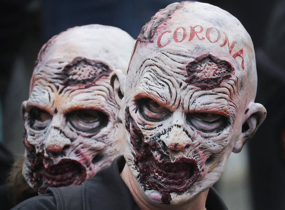 People wearing masks take part in a 'We Do Not Consent' rally at Trafalgar Square, organised by Stop New Normal, to protest against coronavirus restrictions, in London, Saturday, Sept. 26, 2020. (AP Photo/Frank Augstein)