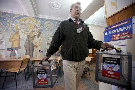 A member of a local electoral commission carries ballot boxes during preparations for the upcoming election, at a polling station in Donetsk, eastern Ukraine November 1, 2014.  REUTERS/Maxim Zmeyev