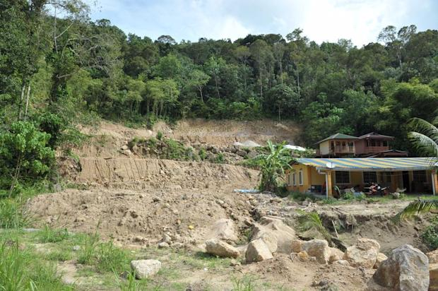 A large swath of hill land has been cleared at Kampung Sungai Rusa with a row of terrace houses built on the bottom and wooden houses on stilts perching on the slopes.