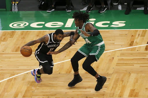 Brooklyn Nets guard Kyrie Irving (11) drives against Boston Celtics center Robert Williams III (44) during the first half of an NBA preseason basketball game, Friday, Dec. 18, 2020, in Boston. (AP Photo/Mary Schwalm)