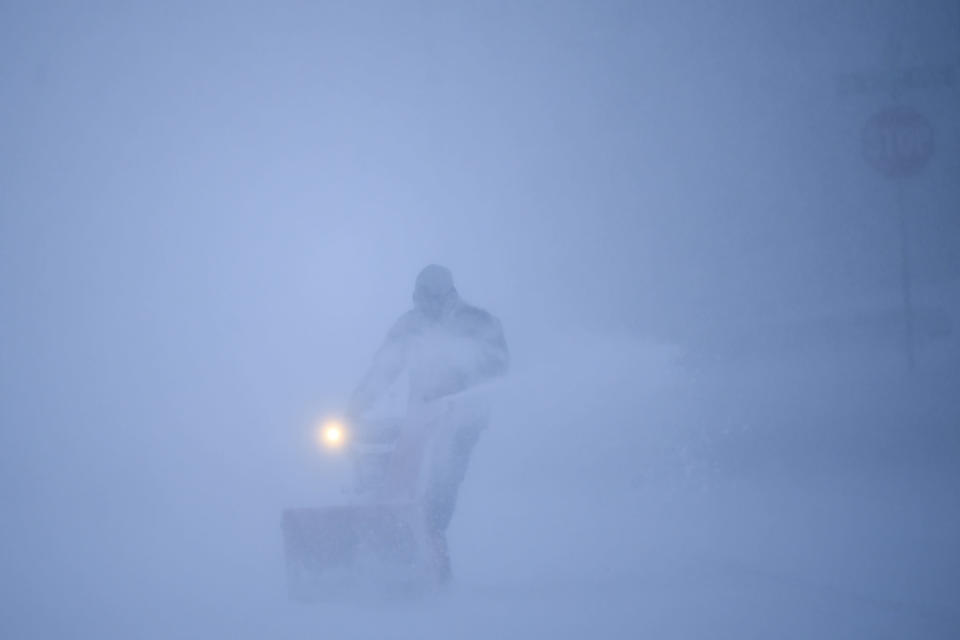 Tim Keefe uses a snow blower to clear his driveway during a snow storm, Wednesday, Dec. 23, 2020 in Robbinsdale, Minn. (Aaron Lavinsky/Star Tribune via AP)