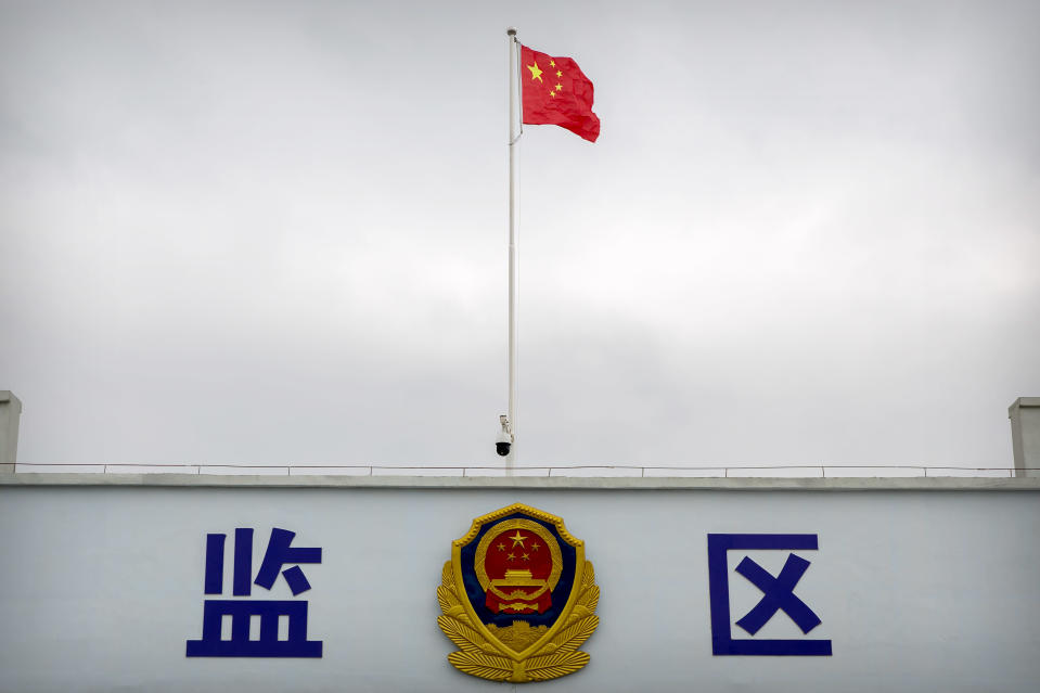 A Chinese national flag flies over a vehicle entrance to the inmate detention area at the Urumqi No. 3 Detention Center in Dabancheng in western China's Xinjiang Uyghur Autonomous Region, on April 23, 2021. (AP Photo/Mark Schiefelbein)