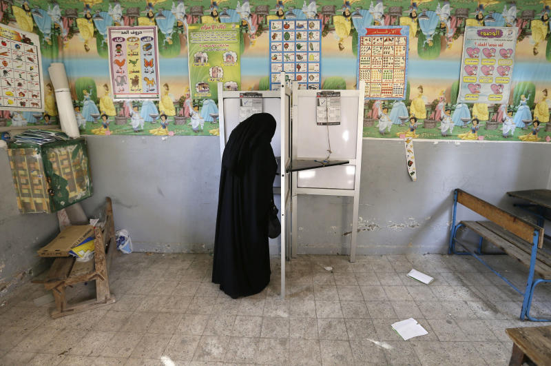 An Egyptian woman casts her vote at polling center during a referendum on a disputed constitution drafted by Islamist supporters of President Mohammed Morsi, in Alexandria, Egypt, Saturday, Dec. 15, 2012. (AP Photo/Hassan Ammar)