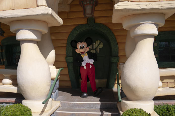 Mickey Mouse keeps social distance while interacting with guests at Disneyland in Anaheim, Calif., Friday, April 30, 2021. The iconic theme park in Southern California that was closed under the state's strict virus rules swung open its gates Friday and some visitors came in cheering and screaming with happiness. (AP Photo/Jae C. Hong)