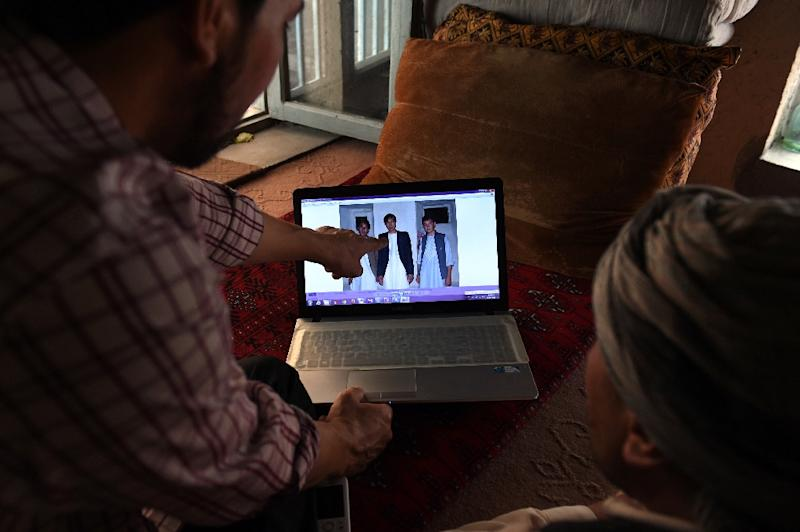 Abdullah Karim Aminy (L), the cousin of Mohammad Shafi Karimi, looks at a photograph of his cousin on a laptop as he talks to a friend in Kabul (AFP Photo/Wakil Kohsar)