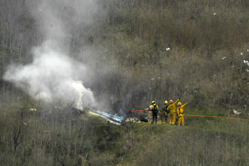 FILE - In this Jan. 26, 2020, file photo, firefighters work the scene of a helicopter crash where former NBA star Kobe Bryant died in Calabasas, Calif. Federal safety investigators bypassed aviation regulators on Tuesday, June 2, 2020, and urged leading helicopter manufacturers to install so-called black boxes that would help determine the cause of crashes such as the one that killed former NBA star Kobe Bryant.  (AP Photo/Mark J. Terrill, File)