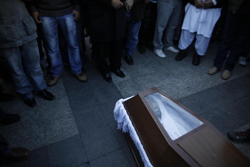 Mourners  gather in front of the coffin carrying the body of Shehzad Luqman, a Pakistani immigrant who was murdered on Thursday after being stabbed by suspected extreme rightists, during a ceremony  in front of the city Hall in Athens on Saturday, Jan. 19 2013. An estimated 3,000 people marched  through central Athens in protest at a spate of anti-immigrant attacks that turned fatal Thursday when a 27-year-old Pakistani immigrant was stabbed by suspected extreme rightists.  (AP Photo/Kostas Tsironis)