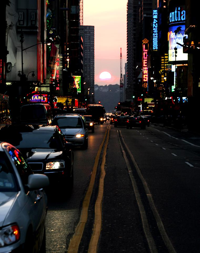 "The setting sun sinks in perfect alignment with New York's 42nd Street July 11, 2005. Since Manhattan's east-west streets don't run precisely east-west, they align with the setting sun only twice a year, an event known locally as ""Manhattanhenge"". REUTERS/Jeff Zelevansky"