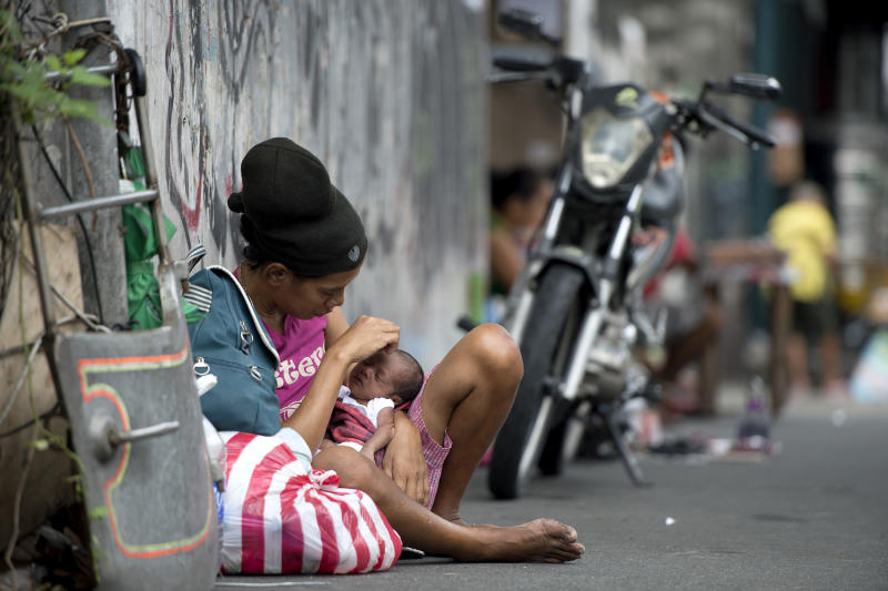A homeless woman cares for her one-month-old baby on a street in the Filipinon capital Manila on August 28, 2014