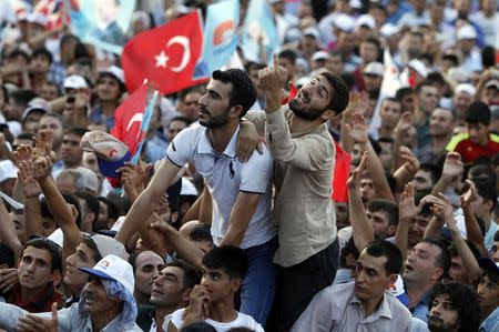 Supporters of Turkey's Prime Minister and presidential candidate Tayyip Erdogan react during an election rally in Diyarbakir