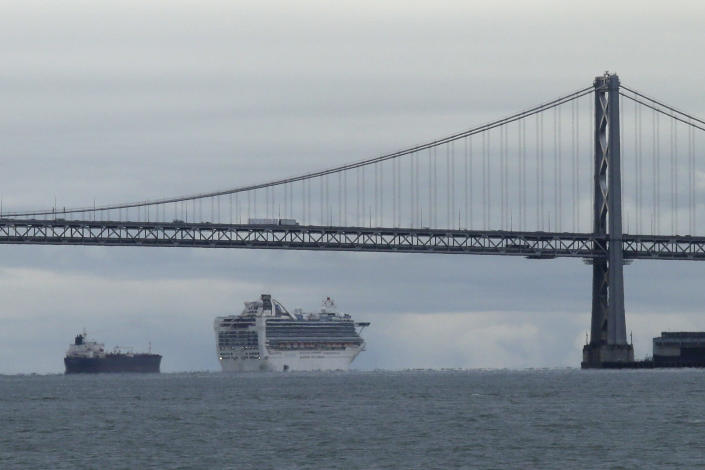 FILE - In this March 16, 2020, file photo framed by the San Francisco-Oakland Bay Bridge, the Grand Princess cruise ship makes its way to an anchorage, in San Francisco. Cruise ships are returning to San Francisco after a 19-month hiatus brought on by the pandemic in what's sure to be a boost to the city's economy, the mayor announced Friday, Oct. 8, 2021. (AP Photo/Eric Risberg,File)