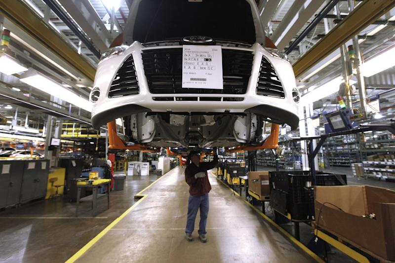 FILE- In this Dec. 14, 2011, file photo, a line worker assembles a 2012 Ford Focus at the Ford Michigan Assembly plant in Wayne, Mich. The plant is one 13 North American factories where Ford Motor Co. will be adding a a week of production in 2012, so the company can make another 40,000 vehicles this year and meet the needs of rising car and truck sales. (AP Photo/Paul Sancya, File)