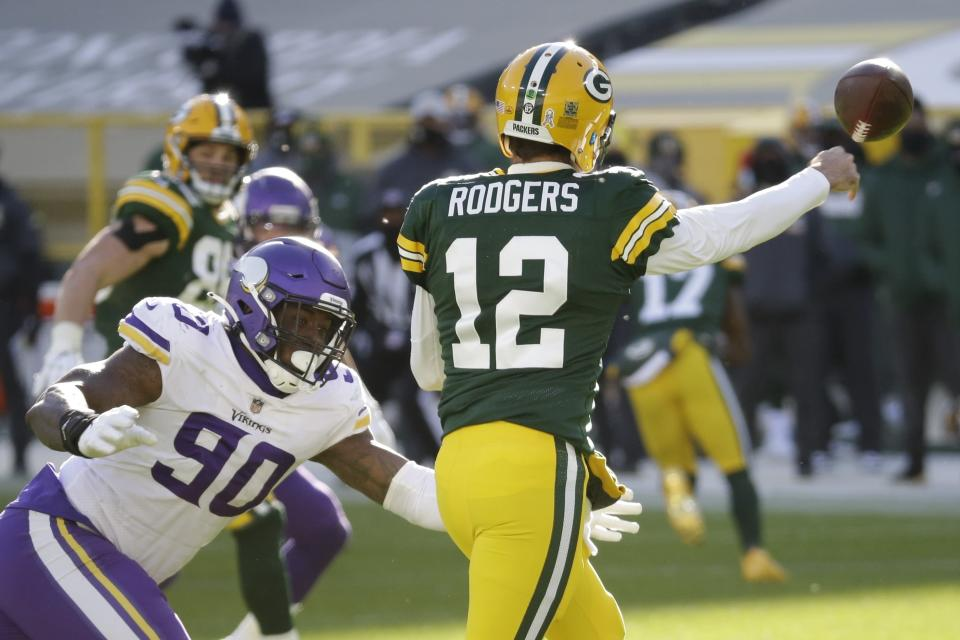 Green Bay Packers' Aaron Rodgers passes with Minnesota Vikings' Jalyn Holmes rushing during the second half of an NFL football game Sunday, Nov. 1, 2020, in Green Bay, Wis. (AP Photo/Mike Roemer)