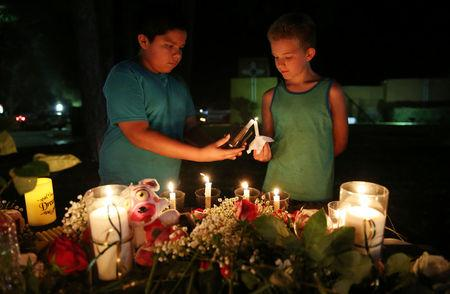Attendees light a candle during a vigil for the victims of a shooting at  Santa Fe