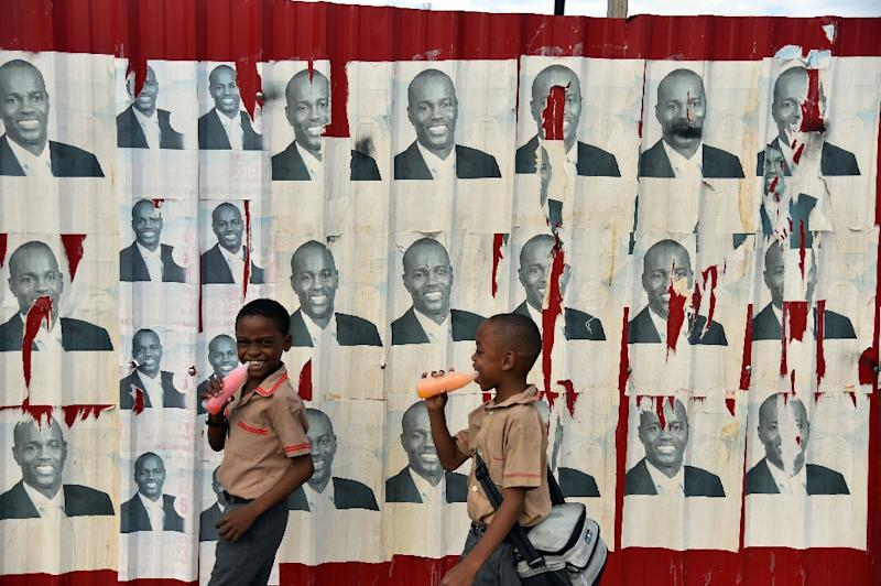 Children walk past election poster of presidential candidate Jovenel Moise of PHTK political party in Port-au-Prince on January 21, 2016 (AFP Photo/Hector Retamal)