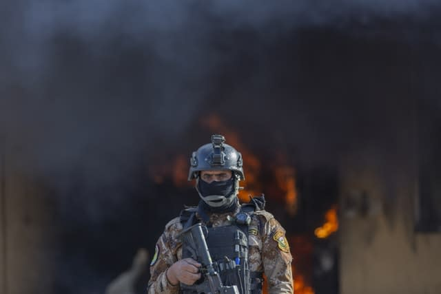 An Iraqi soldier stands guard in front of smoke rising from a fire set by pro-Iranian militiamen and their supporters in the US embassy compound in Baghdad