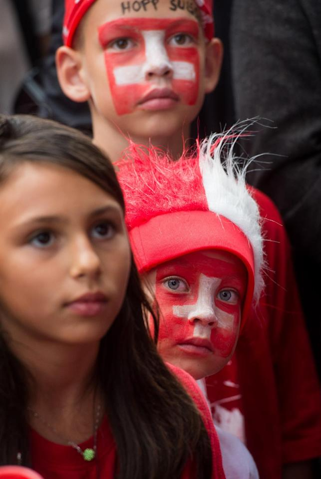 Three young Swiss soccer fans watch a TV screen during the live broadcast of the Brazil Soccer FIFA World Cup match between Switzerland and Argentina at the public viewing zone on the Piazza Manzoni in Lugano, Switzerland, Monday, July 1 2014. (AP Photo/Keystone, Gabriele Putzu)