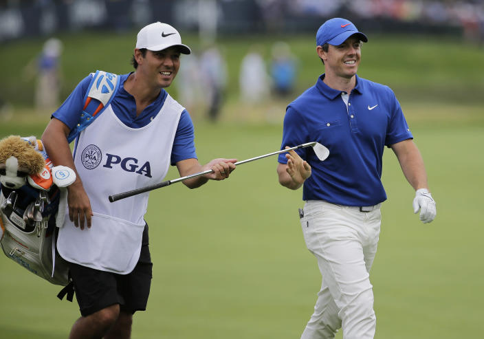 Rory McIlroy, of Northern Ireland, hands an iron to his caddie on the 15th fairway during the final round of the PGA Championship golf tournament, Sunday, May 19, 2019, at Bethpage Black in Farmingdale, N.Y. (AP Photo/Seth Wenig)