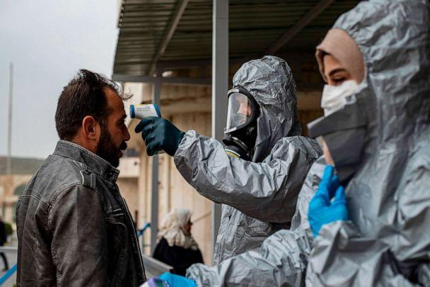 PHOTO: Medics check the body temperature of passengers, as a preventive measure against the coronavirus, upon their arrival by bus in Syria's Kurdish area from Iraqi Kurdistan via the Semalka border crossing in Syria, March 1, 2020. (Delil Souleiman/AFP/Getty Images)