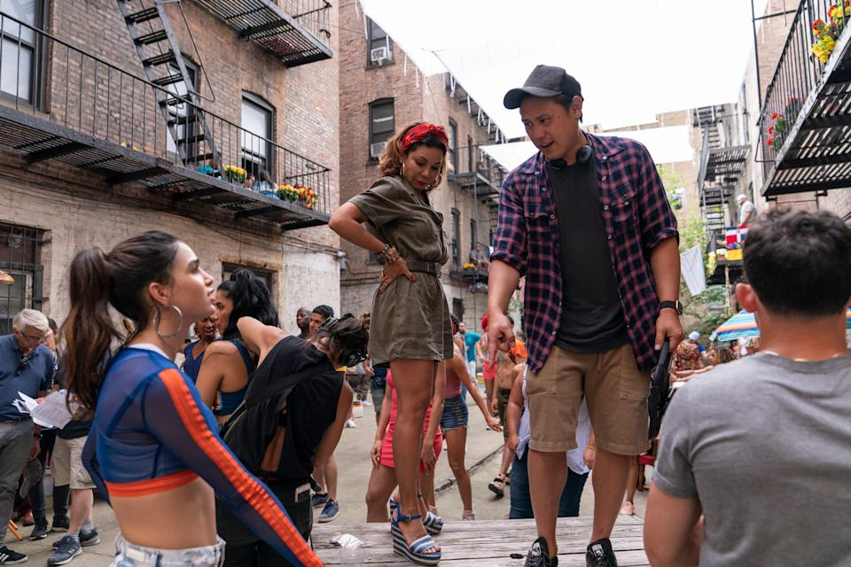 """This image released by Warner Bros. Entertainment shows Melissa Barrera, from left, Daphne Rubin-Vega and director Jon M. Chu on the set of """"In the Heights,"""" in theaters an HBO Max on June 11."""