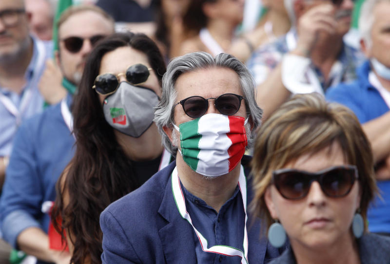 People wear face masks with the colors of the Italian flag as they attend a center-right opposition rally in Rome's central Piazza del Popolo, Saturday, July 4, 2020. (AP Photo/Riccardo De Luca)