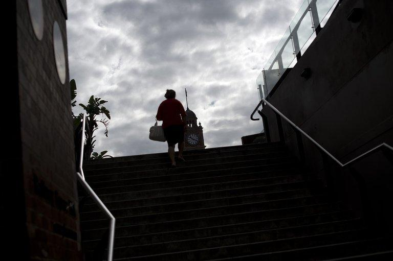 A woman emerges from a underground walkway near the Central train station in the business district of Sydney on April 5, 2013. Australian Prime Minister Julia Gillard on Monday warned voters to brace for an austere election-year budget, unveiling a Aus$12 billion (US$12.4 billion) slump in revenues due to the strong dollar
