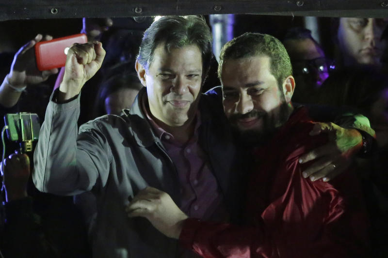 Brazil's presidential candidate for the Workers' Party Fernando Haddad, left, embraces Guilherme Boulos, the former candidate for the Socialism and Liberty Party, during a campaign rally in Sao Paulo, Brazil, Wednesday, Oct. 24, 2018. Haddad will face Jair Bolsonaro, the far-right congressman, in a presidential runoff on Sunday. (AP Photo/Nelson Antoine)