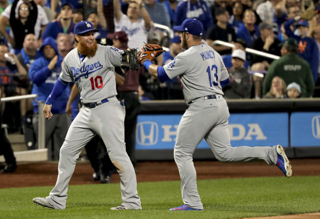 Los Angeles Dodgers third baseman Justin Turner (10) celebrates with second baseman Max Muncy (13) after Muncy turned a double play to end the eighth inning of a baseball game against the New York Mets, Friday, June 22, 2018, in New York. (AP Photo/Julie Jacobson)
