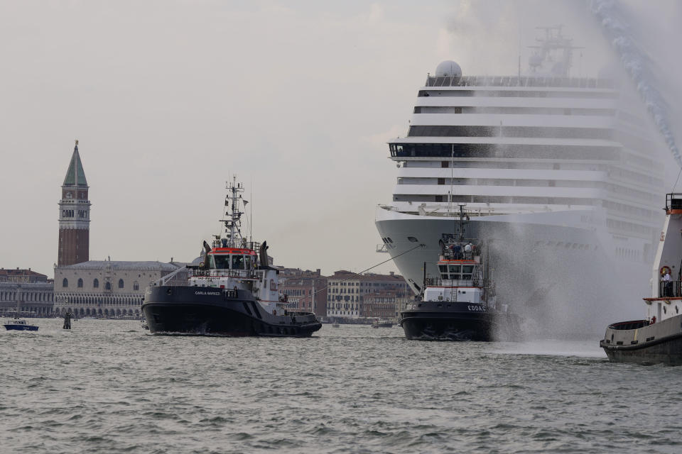 The the 92,409-ton,16-deck MSC Orchestra cruise ship exits the lagoon as St. Mark's Square stands out in background, left, as it leaves Venice, Italy, Saturday, June 5, 2021. The first cruise ship leaving Venice since the pandemic is set to depart Saturday amid protests by activists demanding that the enormous ships be permanently rerouted out the fragile lagoon, especially Giudecca Canal through the city's historic center, due to environmental and safety risks. (AP Photo/Antonio Calanni)