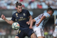 Real Madrid's Gareth Bale, left, challenges for the ball with Celta Vigo's Kevin Vazquez during La Liga soccer match between Celta and Real Madrid at the Balados Stadium in Vigo, Spain, Saturday, Aug. 17, 2019. (AP Photo/Luis Vieira)
