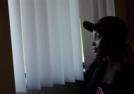 Former adopted child Quita Puchalla looks out the window of her apartment in Milwaukee, Wisconsin