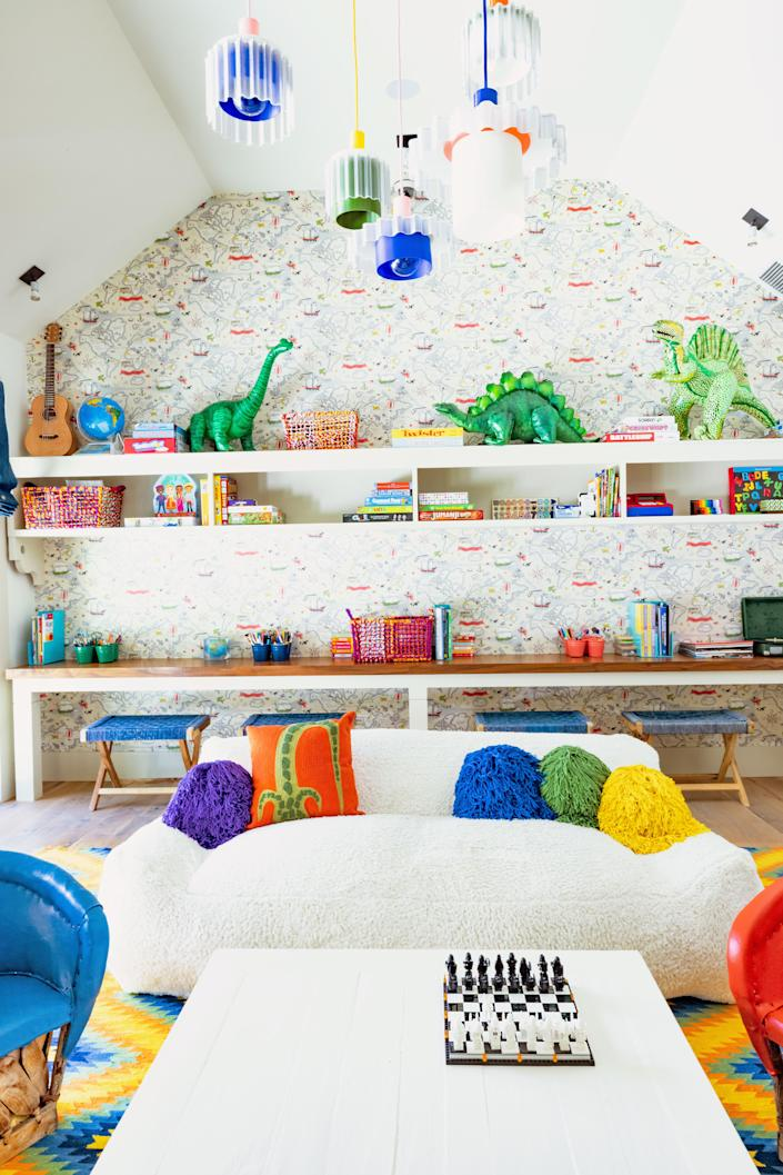 Five recycled-plastic pendants by Warren & Laetitia hang in the kids' playroom above an RH Kids sofa with crochet pillows from Coming Soon NY. The wallpaper is by Walnut. The four indigo benches are from Lost & Found L.A.