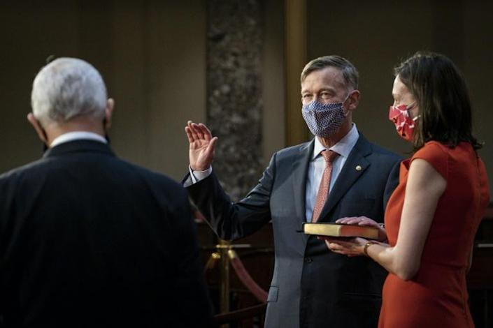Vice President Mike Pence administers the Senate oath of office to John Hickenlooper (D-CO) as his wife, Robin Pringle, holds the Bible during a mock swearing-in ceremony in the Old Senate Chamber on Capitol Hill on January 3, 2021 in Washington, DC
