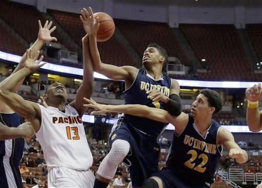 Pacific forward Khalil Kelley (13) loses the ball as UC Irvine's Will Davis II and Damon Starring (22) defend in the first half of the NCAA Big West tournament championship college basketball game in Anaheim, Calif., Saturday, March 16, 2013. (AP Photo/Reed Saxon)