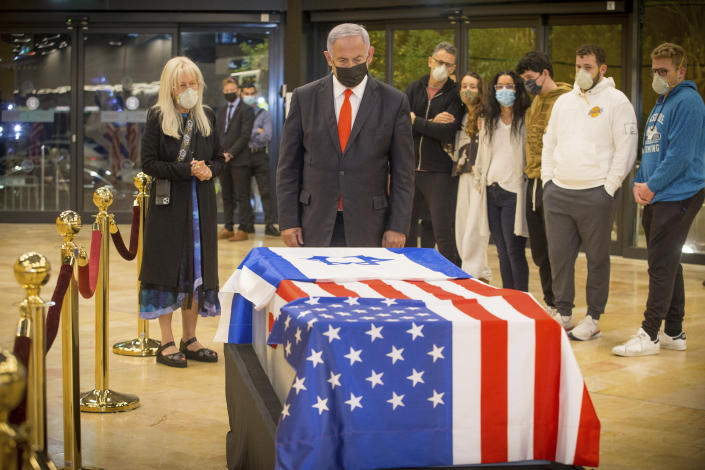 Israeli Prime Minister Benjamin Netanyahu stands before the casket of Sheldon Adelson upon arrival to Ben Gurion Airport, near the city of Lod, Israel, Thursday, Jan. 14, 2021. Adelson's family, including his wife, Miriam, at left, are present. Adelson, the billionaire mogul and power broker who built a casino empire spanning from Las Vegas to China and became a singular force in domestic and international politics has died after a long illness, his wife said Tuesday, Jan. 12, 2021. (Ami Shooman, Israel Hayom/ Pool Photo via AP)