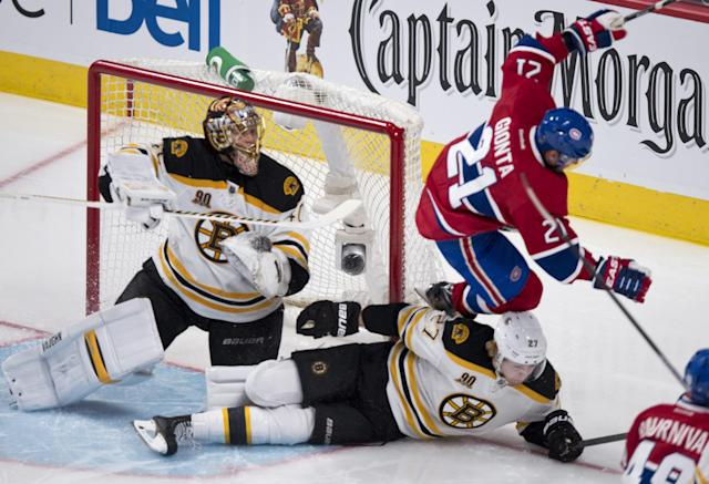 Montreal Canadiens' Brian Gionta leaps over Boston Bruins' Dougie Hamilton next to goalie Tuukka Rask during second period NHL hockey action Thursday, Dec. 5, 2013, in Montreal. (AP Photo/The Canadian Press, Paul Chiasson)