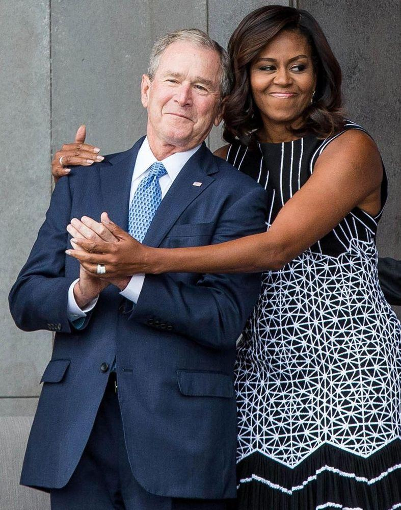 From left: Former President George W. Bush is hugged by former First Lady Michelle Obama in 2016