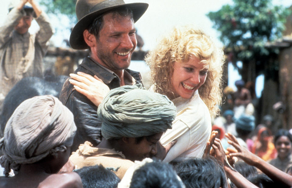 Harrison Ford and Kate Capshaw are greeted by children in a scene from the film 'Indiana Jones And The Temple Of Doom', 1984. (Photo by Paramount/Getty Images)