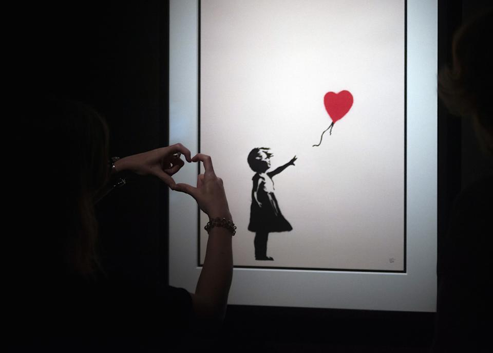 """A woman seen making hand gestures in front of a painting of 'Girl with a balloon' during the exhibition. 'Banksy The art of Protest' at cultural center 'La T�rmica' is an exhibition showing for the first time in Malaga. the work of famous and mysterious British street artist 'Banksy', display more than 40 creations such originals works, sculptures, videos and photographs provide by international private collections including the original print of """"Ni�a con globo"""". (Photo by Jesus Merida Luque / SOPA Images/Sipa USA)"""