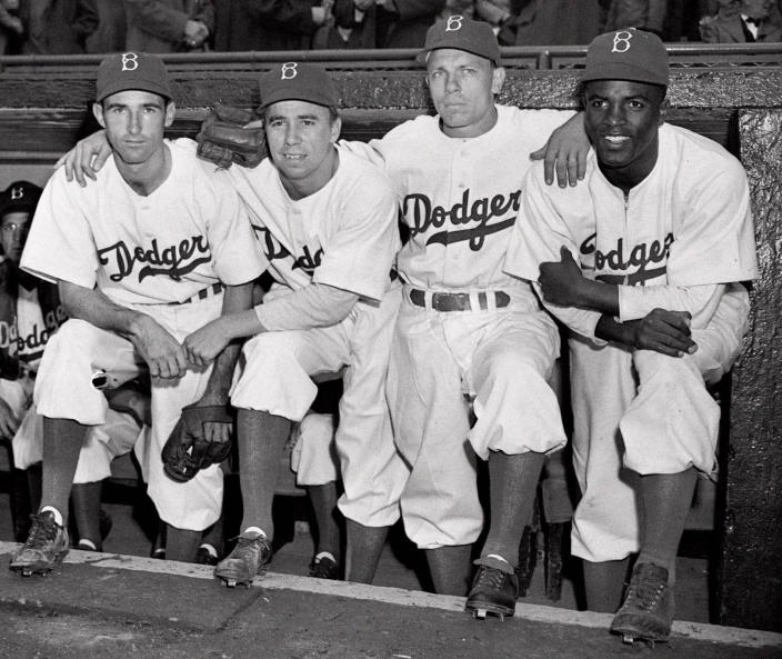 FILE - From left, Brooklyn Dodgers third baseman John Jorgensen, shortstop Pee Wee Reese, second baseman Ed Stanky, and first baseman Jackie Robinson pose before a baseball game against the Boston Braves at Ebbets Field in Brooklyn, N.Y., in this April 15, 1947, file photo. All players, managers, coaches and umpires will wear No. 42 on Thursday, April 15, 2021, to celebrate Jackie Robinson Day, marking the anniversary of the date the Brooklyn Dodgers Hall of Famer made his Major League Baseball debut and broke the sport's color barrier in 1947. (AP Photo/Harry Harris, File)
