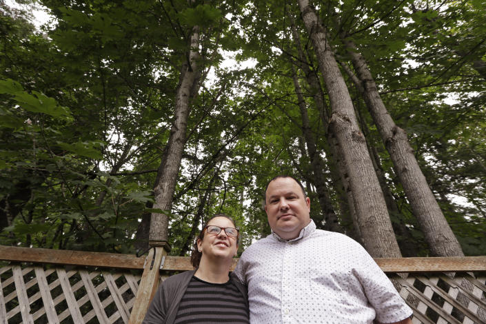 In this photo taken Friday, Aug. 2, 2019, Amy and Jason Ritchie stand in the backyard of their home, adjacent to a forest of conifer and deciduous trees towering overhead in Sammamish, Wash. The Ritchie's had a fire in the woods behind their property four years ago, which drove home the risks of their neighborhood with houses built steps from the woods' edge but only two main routes out. (AP Photo/Elaine Thompson)