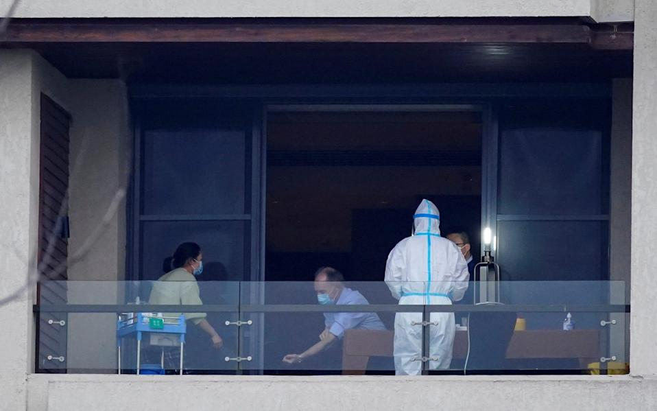 A member of the World Health Organisation team tasked with investigating the origins of Sars-Cov-2 undergoes a blood test on the balcony of his hotel - REUTERS/Aly Song