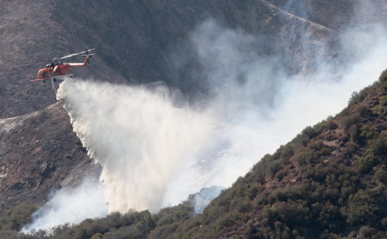 A firefighting helicopter drops water on a wildfire in the Angeles National Forest north of Glendora, Calif., Monday, Sept. 3, 2012. A day after the wildfire broke out near a campground and forced the evacuation of thousands of campers and picnickers it had grown to more than 4,100 acres, or roughly 6 square miles, and was just five percent contained. (AP Photo/Jason Redmond)