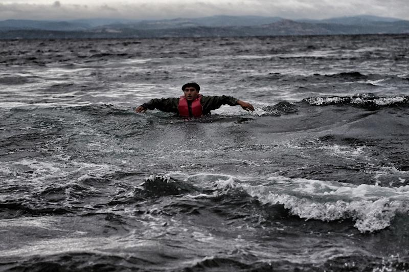A migrant tries to reach the shore as he arrives, with other refugees and migrants, on the Greek island of Lesbos, on October 24, 2015, after crossing the Aegean sea from Turkey (AFP Photo/Aris Messinis)