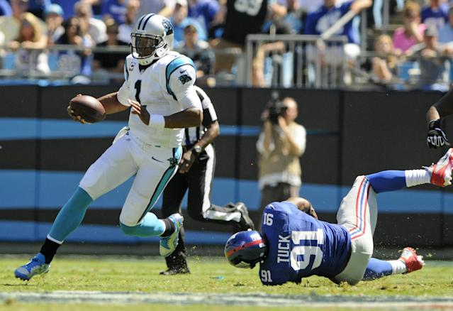Carolina Panthers quarterback Cam Newton (1) scrambles past New York Giants defensive end Justin Tuck (91) during the first half of an NFL football game in Charlotte, N.C., Sunday, Sept. 22, 2013. (AP Photo/Mike McCarn)