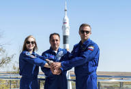 In this handout photo released by Roscosmos, Actress Yulia Peresild, left, director Klim Shipenko' right, and cosmonaut Anton Shkaplerov, members of the prime crew of Soyuz MS-19 spaceship pose at the Russian launch facility in the Baikonur Cosmodrome, Kazakhstan, Monday, Sept. 27, 2021. PIn a historic first, Russia is set to launch an actress and a film director to space to make a feature film in orbit. Actress Yulia Peresild and director Klim Shipenko are set to blast off Tuesday for the International Space Station in a Russian Soyuz spacecraft together with Anton Shkaplerov, a veteran of three space missions. (Andrey Shelepin, Roscosmos Space Agency via AP)